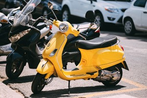 Yellow motorbike, motorcycle scooter parked in city.
